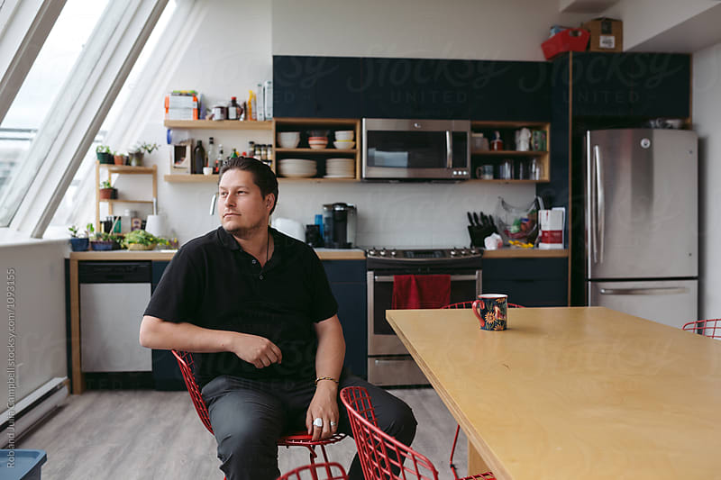 Portrait of young man sitting at table thinking by Rob and Julia Campbell for Stocksy United
