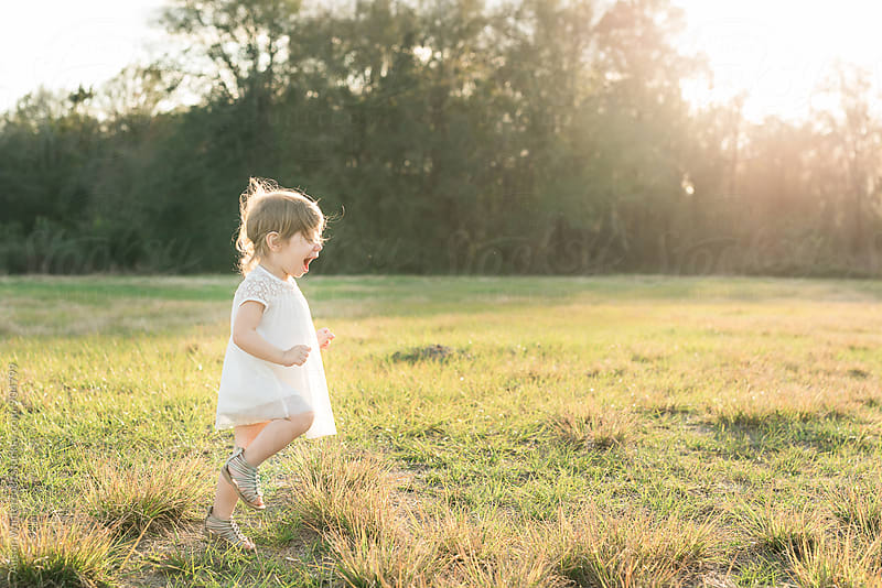 A Young Girl Running Through A Field by Alison Winterroth for Stocksy United