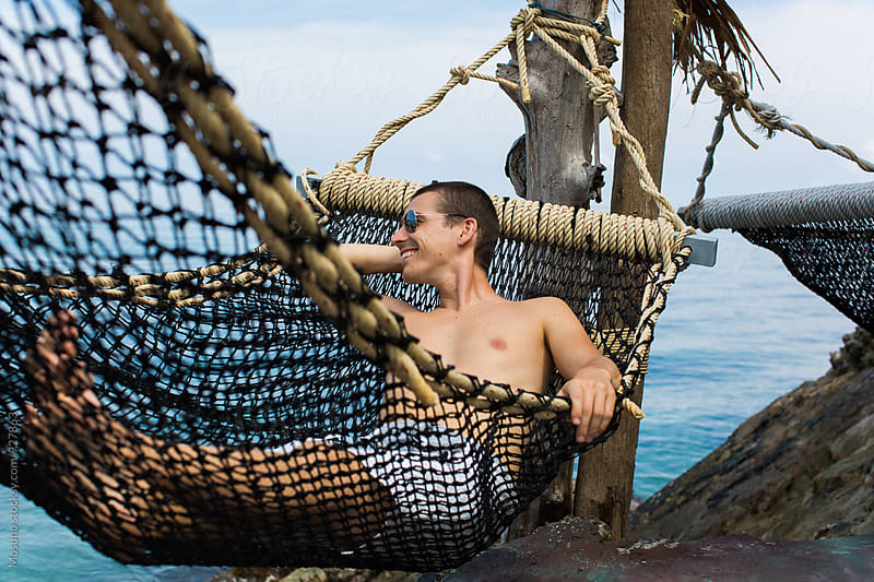 Man Relaxing in a Hammock by the Sea by Mosuno for Stocksy United