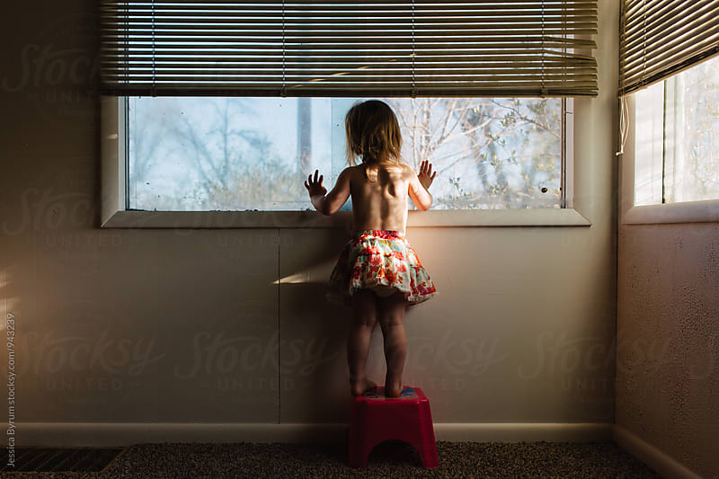 Toddler girl with hands on window  by Jessica Byrum for Stocksy United