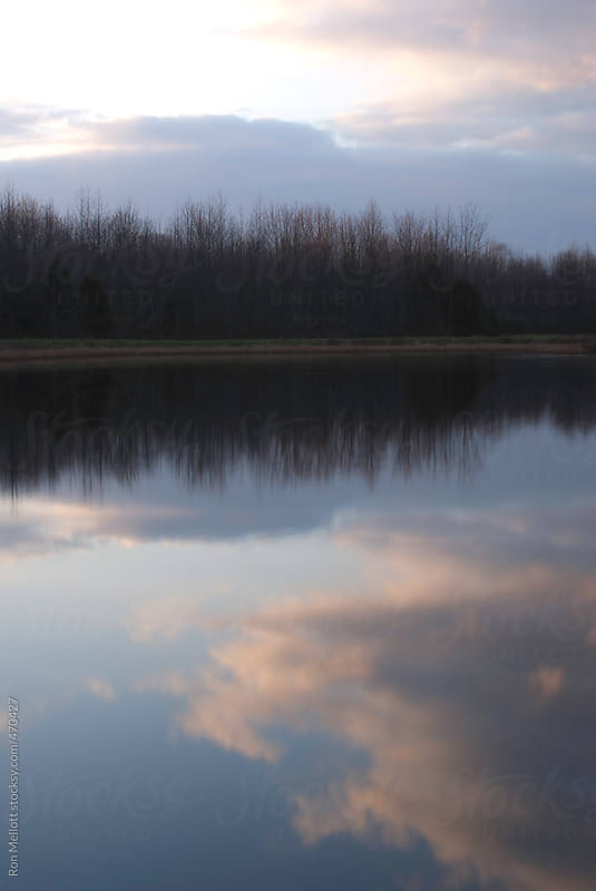 telephoto of sunset on Alice Lake in Indiana clouds reflecting in calm waters of lake by Ron Mellott for Stocksy United
