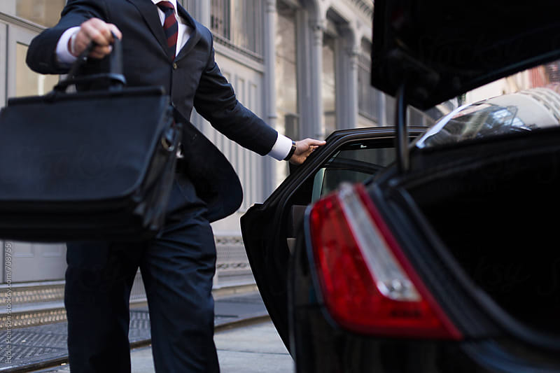 Closeup shot of a business man putting his suitcase in the trunk by Eddie Pearson for Stocksy United