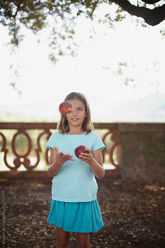 Little girl playing and juggling with fresh fruit by Miquel Llonch for Stocksy United