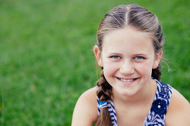 Young Girl with Braids Smiling by Holly Clark for Stocksy United