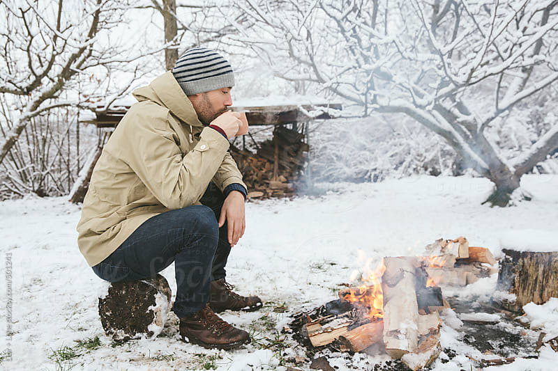 Man drinking hot drink next to bonfire in the snow by Lior + Lone for Stocksy United