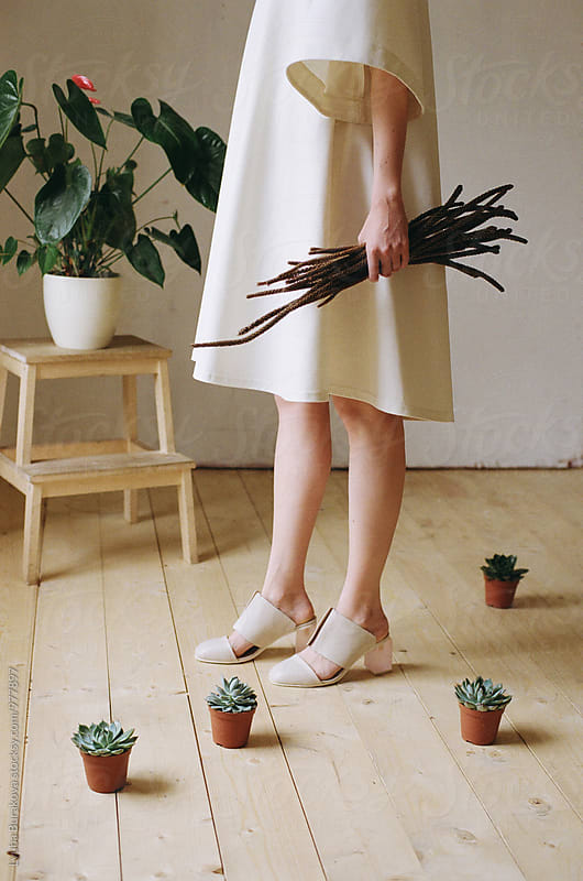 Fashion shot of a woman against plants by Lyuba Burakova for Stocksy United