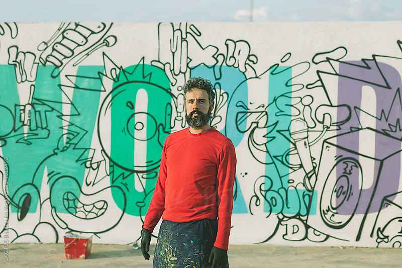 Man painting in a graffiti wall by Blai Baules for Stocksy United