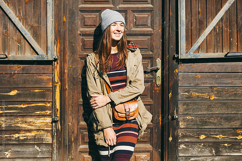 Hipster woman smiling standing in front of a wooden cabin in the mountain. by BONNINSTUDIO for Stocksy United
