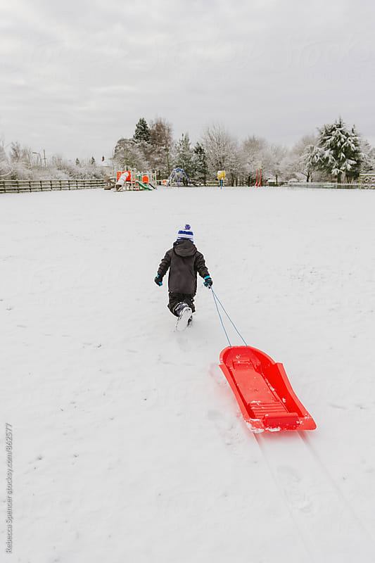 Young boy pulls his toboggan across the snow towards a play park by Rebecca Spencer for Stocksy United