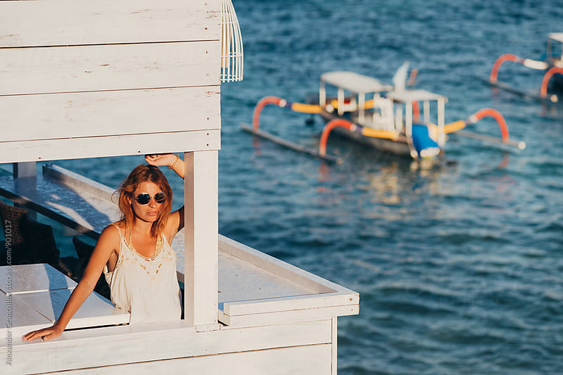 Woman On Balcony At Seaside by Alexander Grabchilev for Stocksy United