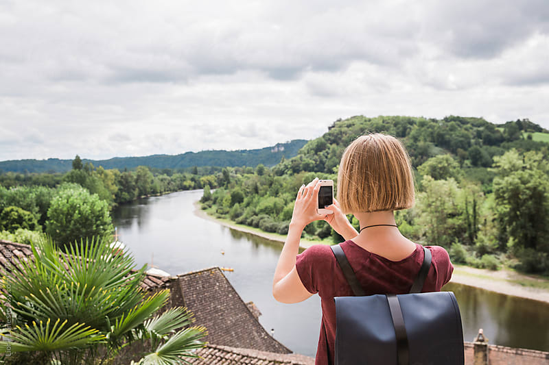 Young blond woman taking a landscape picture on her phone by Lior + Lone for Stocksy United