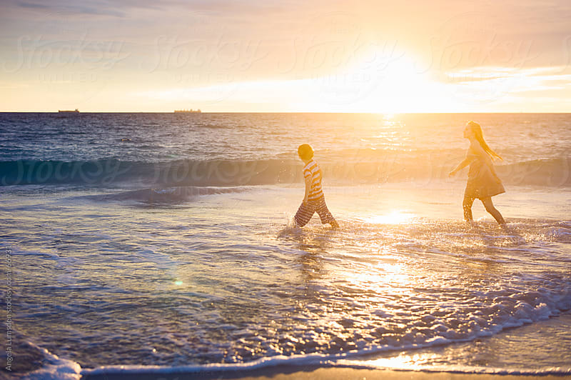 Boy and girl splashing at the beach by Angela Lumsden for Stocksy United