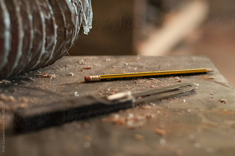 A pencil and slide rule sit on a carpenters workbench by Andy Campbell for Stocksy United