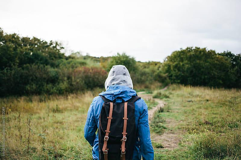 Man walking through the dunes with a hoody on and a backpack by Ivo de Bruijn for Stocksy United