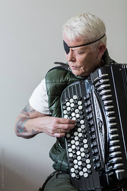 Tattooed senior woman with eye patch focused playing accordion by Lior + Lone for Stocksy United