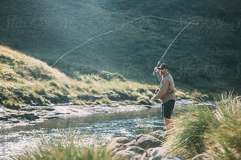 fly fisherman castin in early morning light along a mountain river by Micky Wiswedel for Stocksy United