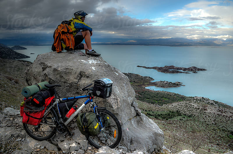 Young cyclist sitting on top of the rock and looking at big lake by Martin Matej for Stocksy United