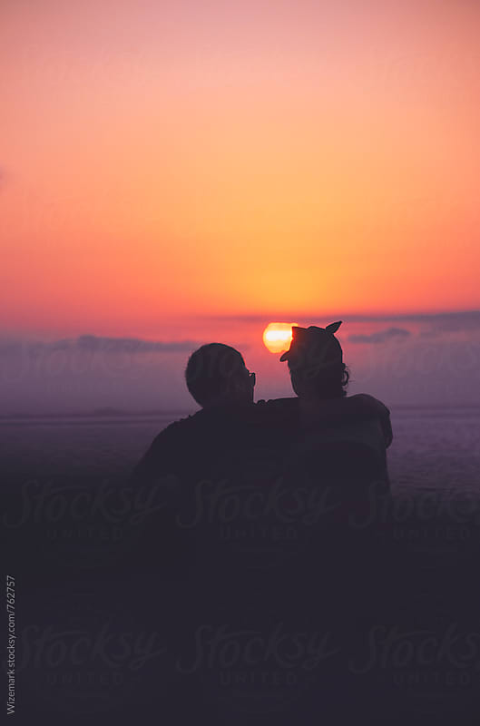 Anonymous, unrecognizable silhouetted couple watching beautiful sunset by Srdjan Kirtic for Stocksy United