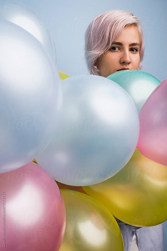 Portrait of beautiful young girl with colorful balloons by Danil Nevsky for Stocksy United