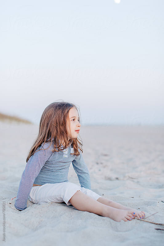 Cute young girl sitting on a beach by Jakob for Stocksy United