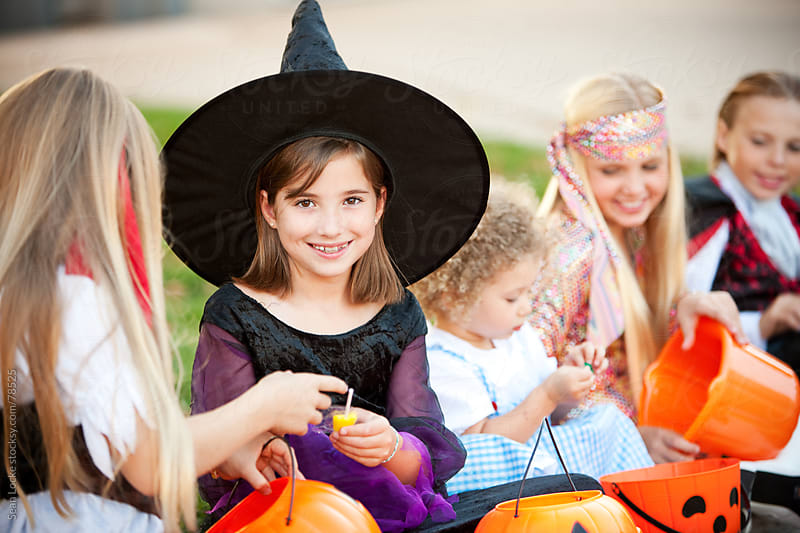 Halloween: Witch Sits with Friends on Halloween by Sean Locke for Stocksy United