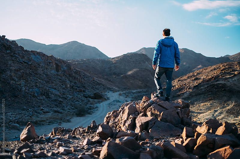 Hiker on a rocky outcrop in a desert landscape overlooking a dirt track into the horizon by Micky Wiswedel for Stocksy United