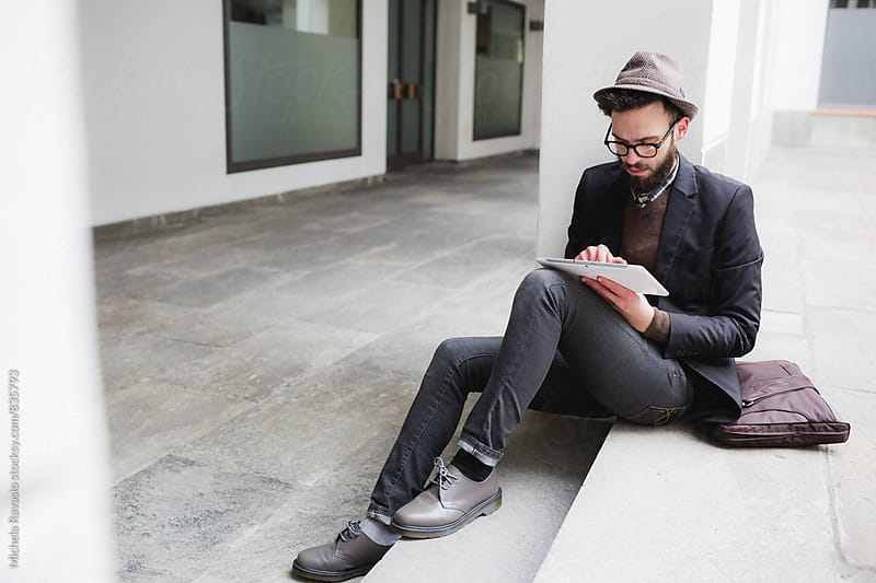 Man with beard using digital tablet by michela ravasio for Stocksy United