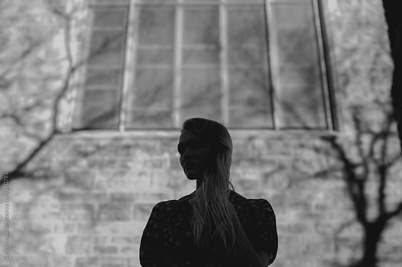 Black and White Silhouette of Girl in front of Brick Building by Gabrielle Lutze for Stocksy United