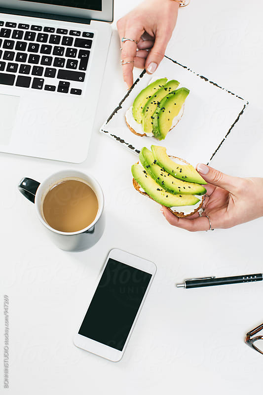 Woman's hands holding an avocado toast for breakfast. by BONNINSTUDIO for Stocksy United