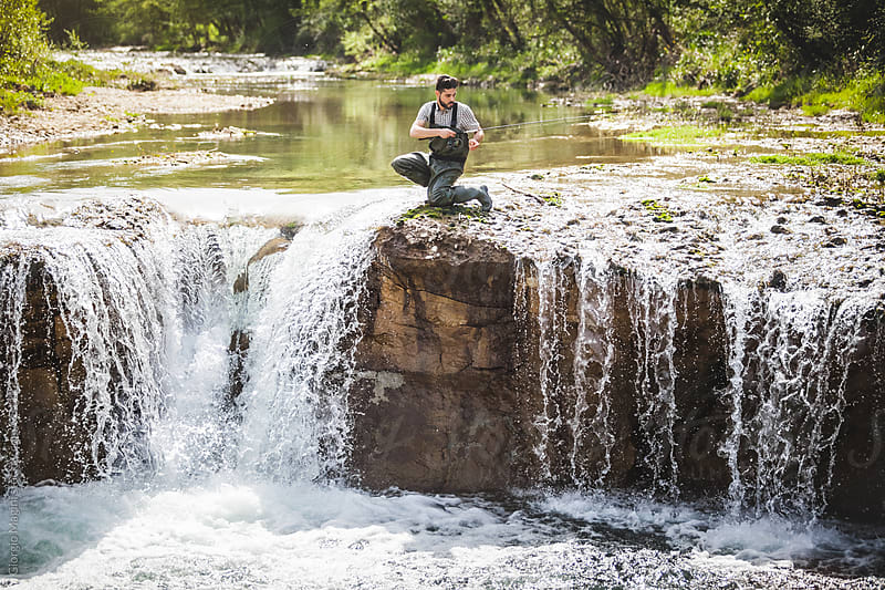 Young Man Fishing upon a Waterfall by Giorgio Magini for Stocksy United