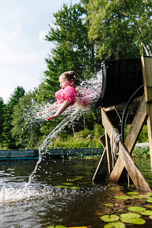 child having fun on water slide at lake by Raymond Forbes LLC for Stocksy United