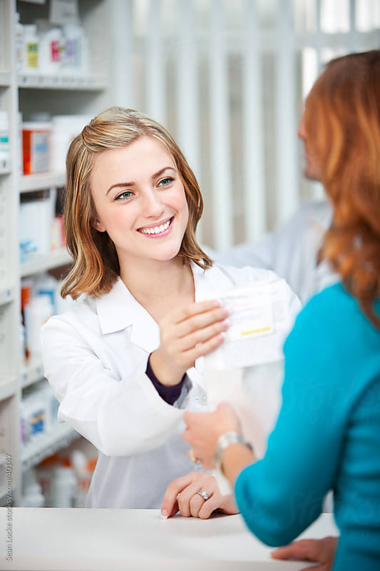 Pharmacy: Handing a Prescription to the Customer by Sean Locke for Stocksy United