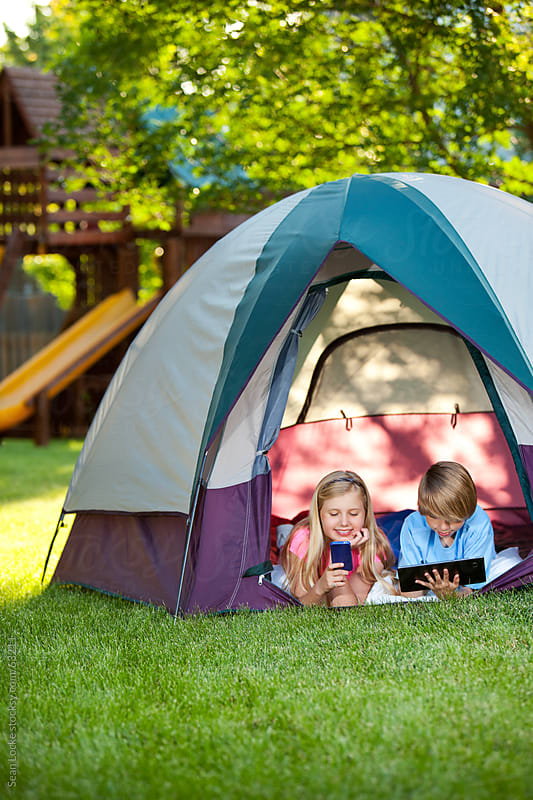 Camping: Kids in Tent with Phone and Computer Instead of Playing by Sean Locke for Stocksy United