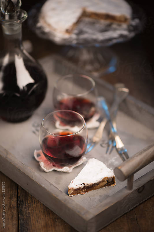 a slice of Panforte and glasses of Marsala wine by Laura Adani for Stocksy United