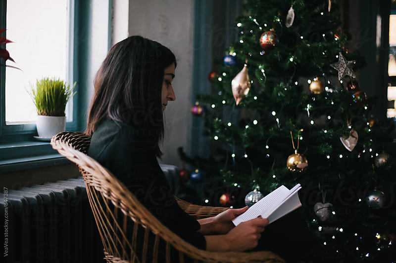Woman reading a book sitting next to a Christmas tree by Marija Mandic for Stocksy United