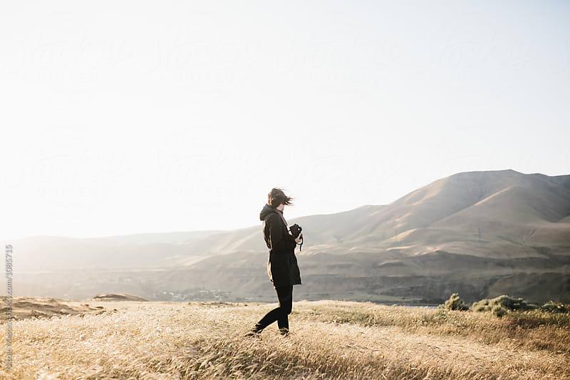 woman exploring mountainous desert landscape at sunset by Nicole Mason for Stocksy United