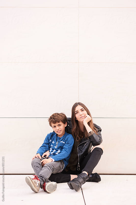 Brother and his older sister sitting against of white wall by Guille Faingold for Stocksy United