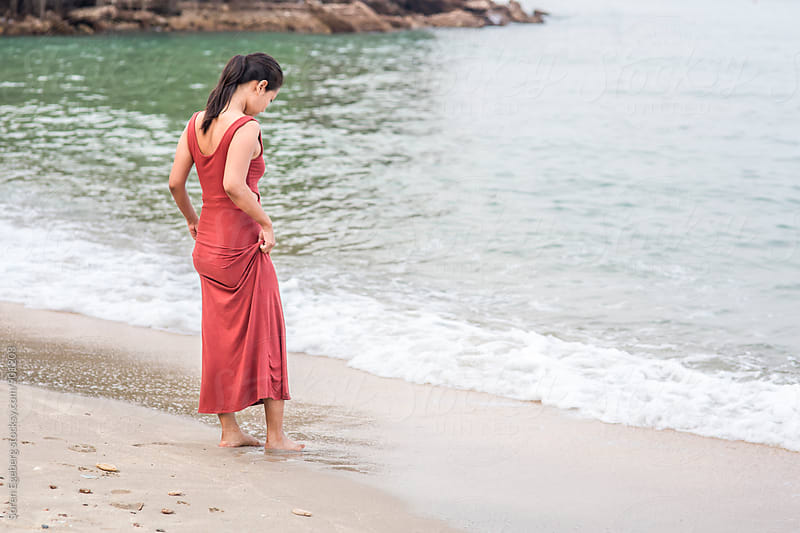 Beautiful asian girl standing by water edge on the beach wearing red dress by Soren Egeberg for Stocksy United