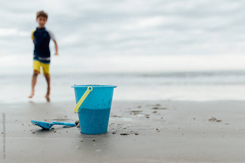 blue bucket and spade on the beach , boy in background  by Léa Jones for Stocksy United