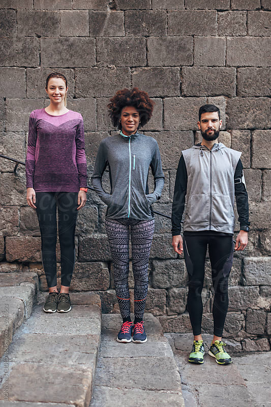 Young multiethnic runners standing in front old wall.  by BONNINSTUDIO for Stocksy United