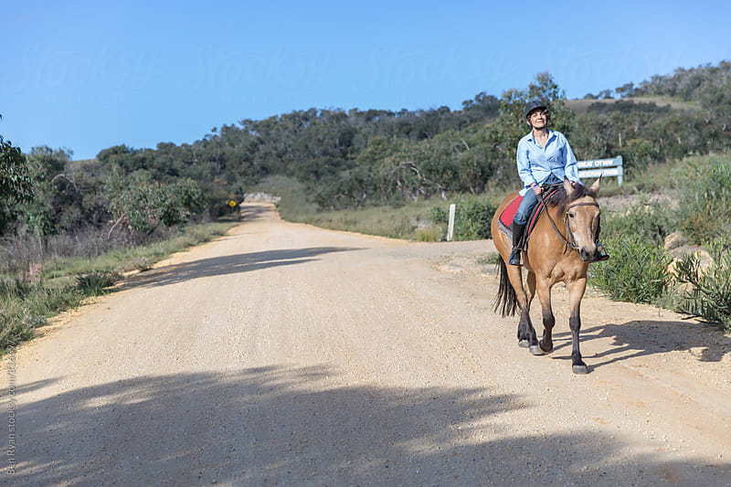 Senior female rider and horse on gravel road by Ben Ryan for Stocksy United