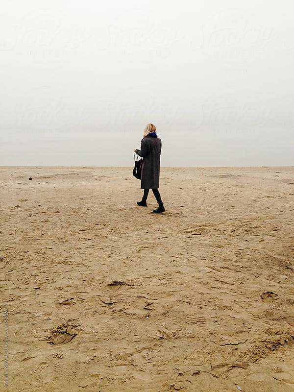 Blonde woman walking on the beach, vertical by Marija Kovac for Stocksy United