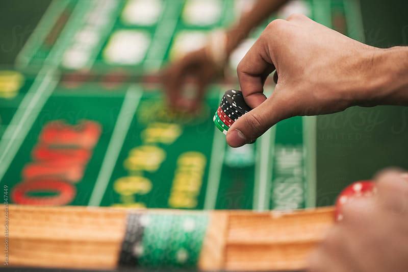Casino: Man Placing Bet In Game Of Craps by Sean Locke for Stocksy United