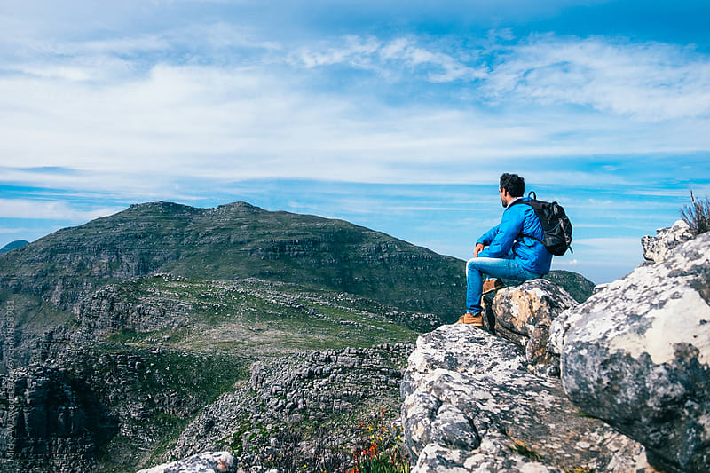 Hiker sitting on a rocky mountain summit enjoying a scenic view by Micky Wiswedel for Stocksy United