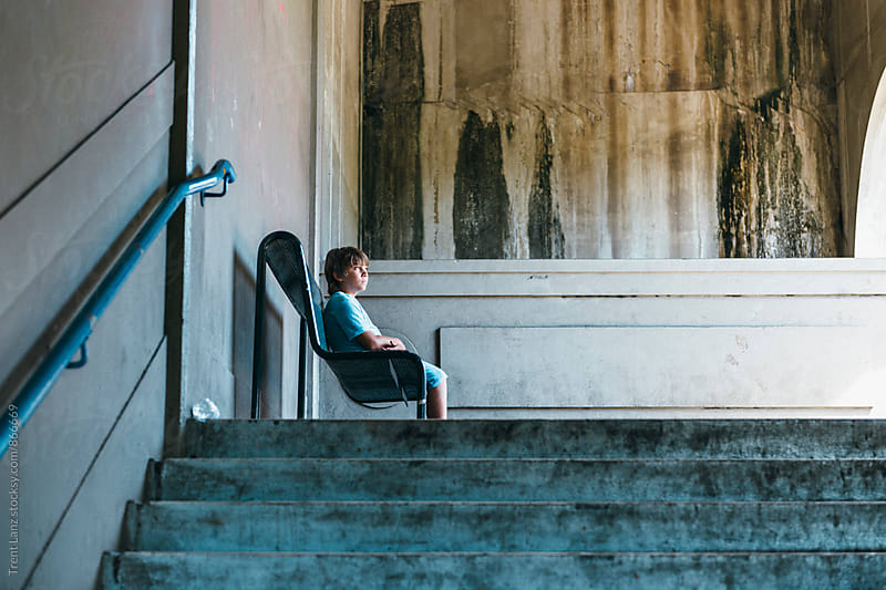 Boy sitting on chair thinking and looking away by Trent Lanz for Stocksy United