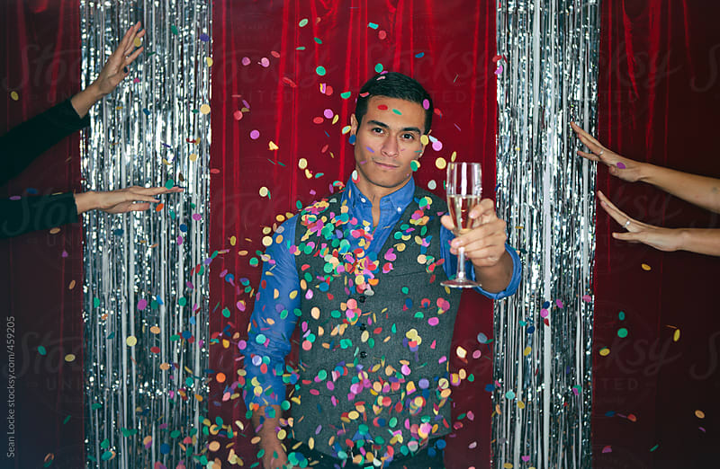Party: Man With Champagne Looks Serious At Women Throw Confetti by Sean Locke for Stocksy United