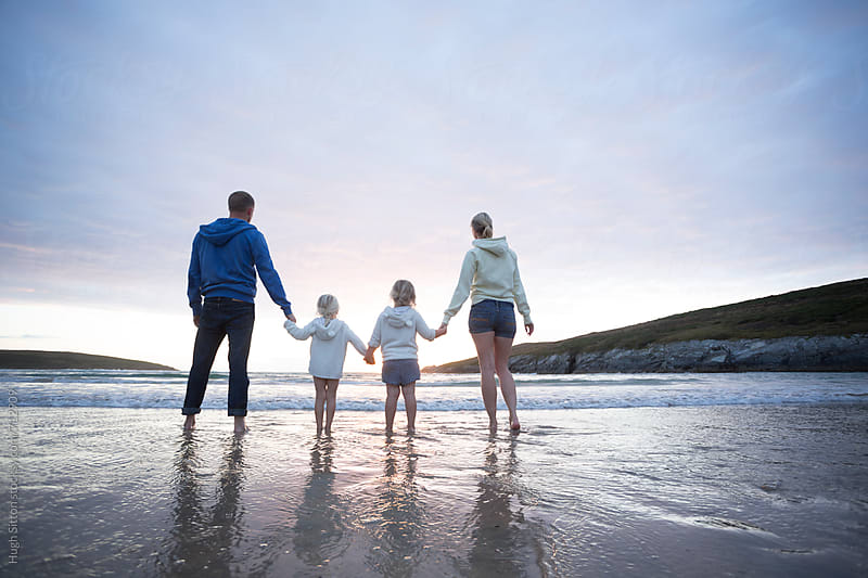 Family at beach watching sunset. by Hugh Sitton for Stocksy United