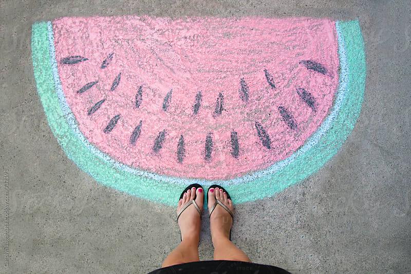 Female standing over a large chalk drawn watermelon by Carolyn Lagattuta for Stocksy United