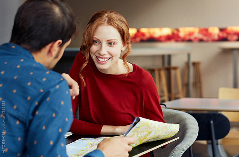 Couple With Map Discussing In Restaurant by ALTO IMAGES for Stocksy United