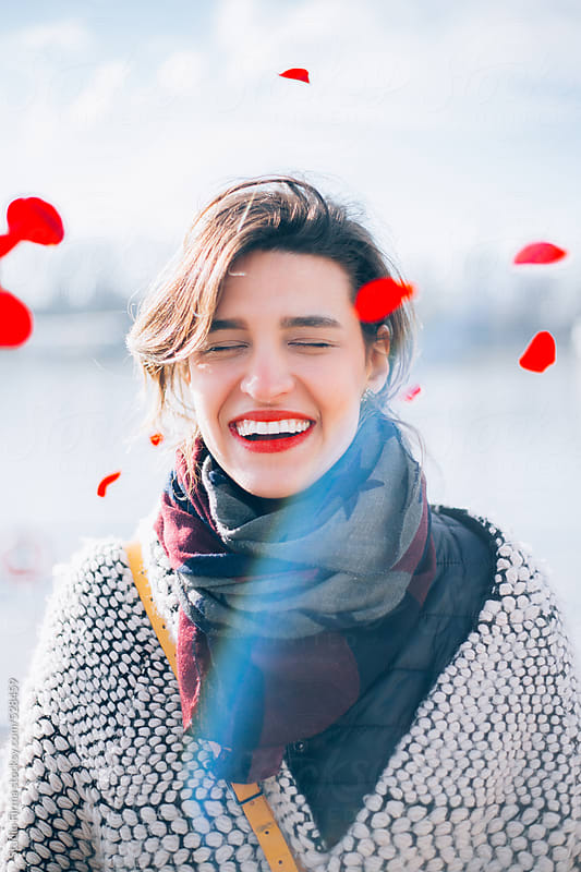 Smiling Woman with flying roses. by Studio Firma for Stocksy United